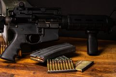 AR rifle 5.56 ammunition. Dark setting with an AR rifle with 5.56 ammunition and magazines Royalty Free Stock Photo