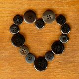 Dark sewing buttons forming a heart Stock Images