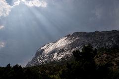 Dark shiny moutain. Rays above the black cliff Royalty Free Stock Photos