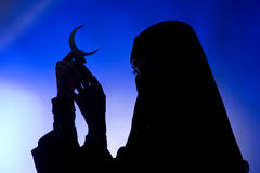 Dark silhouette: Beautiful muslim girl holding a moon symbol Royalty Free Stock Image