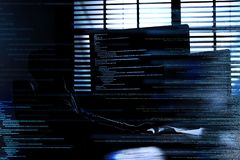 Dark silhouette of cyber criminal hacking computer behind stock image
