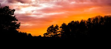 Dark silhouette of a forest landscape at sunset, sundown giving a colorful glow in the sky and clouds stock photos