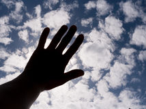 Dark silhouette of hand is closing sun on blue sky with clouds. Stock Photos