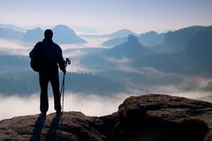 Dark silhouette of hiker with poles in hand. Sunny spring daybreak in rocky mountains. Hiker with sporty backpack stand on rocky p Royalty Free Stock Photo