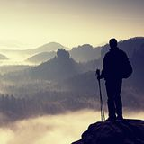 Dark silhouette of hiker with poles in hand. Sunny spring daybreak in rocky mountains. Hiker with sporty backpack stand on rocky p Royalty Free Stock Image
