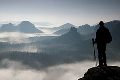 Dark silhouette of hiker with poles in hand. Sunny spring daybreak in rocky mountains. Hiker with sporty backpack stand on rocky p Royalty Free Stock Images