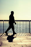 Dark silhouette of a man walking. A dark silhouette of an unrecognisable man walking along a beach promenade at summer sunrise Stock Photo