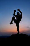 Dark silhouette of a muscular male boxer outdoors on sunset Royalty Free Stock Photos
