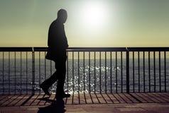 Dark silhouette of a old man walking. A dark silhouette of an unrecognizable man walking along a beach promenade in summer sunrise Royalty Free Stock Image