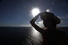 Dark silhouette opposite sun. woman walking in hat, closeup portrait, coast on Lanzarote, Canary Islands, Spain, summer Stock Photos