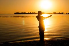 Silhouette of woman dancing tradition trible oriental near big river coast at dawn royalty free stock photography