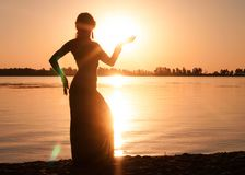 Dark silhouette of woman dancing trible near river coast stock photo