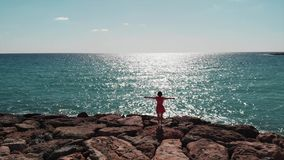 Dark silhouette of woman in red dress with arms apart in air standing on rocky beach pier against sun. Sun road reflection on blue stock video footage