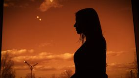 Dark silhouette of a woman standing in profile on twilight backcloth near the window. Outline of female body against. Dark silhouette of a long-haired woman stock footage