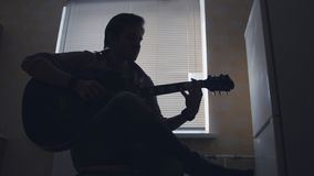 Dark silhouette of young attractive man musician composes music on the guitar and plays, silhouette. Close up Stock Photo