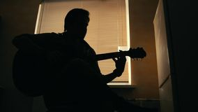 Dark silhouette of young attractive man musician composes music on the guitar and plays, other musical instrument in the. Dark silhouette of young attractive man stock video footage