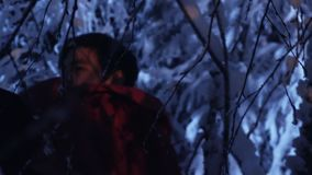 Dark silhouette of young male wandering in snowy winter forest at silent night. stock video