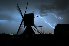 Windmill silhouette with powerful lightning bolts streaking through the sky during a severe thunderstorm in Holland royalty free stock photos
