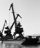 Dark silhouettes of industrial port cranes, Danube River Stock Photo