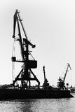 Dark silhouettes of industrial port cranes. Danube River Stock Photography