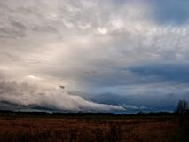 Dark, sinister clouds over the plain. Evening sky covered with a layer of dark, ominous, rainy clouds. It`s evening. Sunlight turns red. The bottom is covered royalty free stock photography