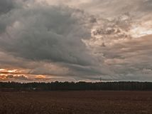 Dark, sinister clouds over the plain. Evening sky covered with a layer of dark, ominous, rainy clouds. It`s evening. Sunlight turns red. The bottom is covered stock photography