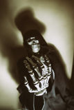 Dark Skeleton Hand Skull Blur. Skeleton in hoodie with hand reaching out as if begging or reaching for viewer. Shot with spot lighting and edited with vintage royalty free stock images