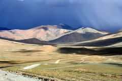 Dark skies over Tibetan plateau. Mountain road through the high central Tibetan plateau, Tibet, China Royalty Free Stock Image