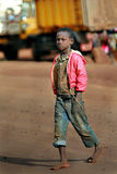 Dark skinned African boy walking barefoot in dirty jeans. Makuyuni, Arusha, Tanzania - February 13, 2008: Unknown African barefoot black gamin boy in pink royalty free stock photography