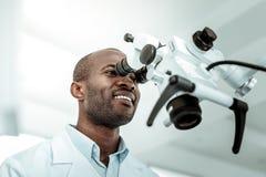 Dark-skinned attractive dentist enjoying his important job. Giant microscope. Dark-skinned attractive dentist enjoying his important job and wearing uniform stock images