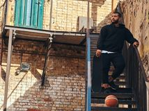 Dark skinned bearded hipster guy dressed in a black hoodie and sports shorts holds a skateboard while standing on stairs. In a ghetto Stock Images