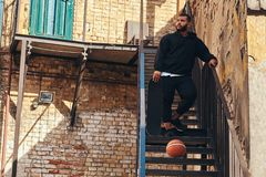 Dark skinned bearded hipster guy dressed in a black hoodie and sports shorts holds a skateboard while standing on stairs. In a ghetto Royalty Free Stock Photography