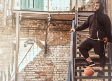 Dark skinned bearded hipster guy dressed in a black hoodie and sports shorts holds a skateboard while standing on stairs. In a ghetto Royalty Free Stock Photo