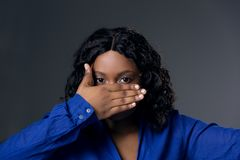 Dark-skinned beautiful girl covers her mouth and face with her hand royalty free stock image