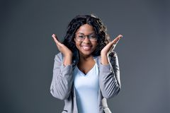 Dark-skinned beautiful girl  in round glasses and a gray jacket joyfully smiles happily raising her hands to his face stock photo
