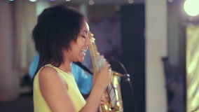 Dark-skinned black woman singer and thin saxophone player performing on stage. stock video footage