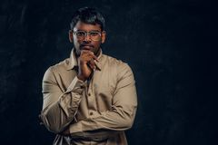 Dark-skinned businessman holding his hand under his chin, posing and looking into the camera royalty free stock image