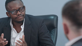 Dark-skinned businessman sitting at table and communicating with his caucasian personal assistant Royalty Free Stock Images