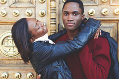 Dark skinned couple having fun while standing outdoors against vintage door, two friends enjoying recreation time Royalty Free Stock Photography