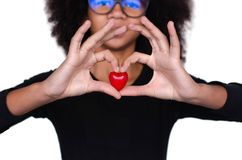Dark-skinned curly girl holding a red heart royalty free stock photo