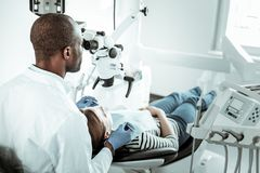 Dark-skinned dentist and his female patient having appointment royalty free stock images