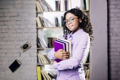 A dark-skinned girl in a blue shirt and round glassesstands against the background of a window and a bookshelf, holds books stock photography