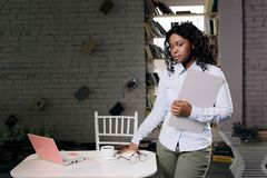 A dark-skinned girl in a blue shirt and round glassesstands against the background of a window and a bookshelf royalty free stock images