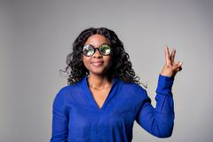 Dark skinned girl with glasses of kaleidoscopes in a blue blouse shows a sign of peace. Isolated on gray background royalty free stock image