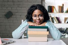 The dark-skinned girl with glasses looking calm and puts her head on the books. stock photos