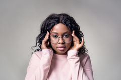 A dark-skinned girl in a pink jacket round glasses touches temples with her hands located on a gray background. Looks at camera royalty free stock photos
