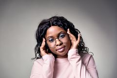 A dark-skinned girl in a pink jacket round glasses touches temples with her hands located on a gray background. Looks at camera head bowed slightly stock photography