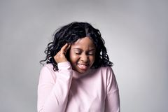 A dark-skinned girl in a pink jacket touches her temples with her hands, her face is distorted by pain. It is located on a gray background stock photography