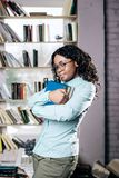 A dark-skinned girl in a spectacled and blue shirt stands against the background of a window and a bookshelf, stock photos