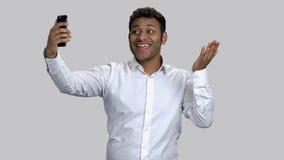 Dark-skinned guy taking selfies on his frontal camera and posing.
